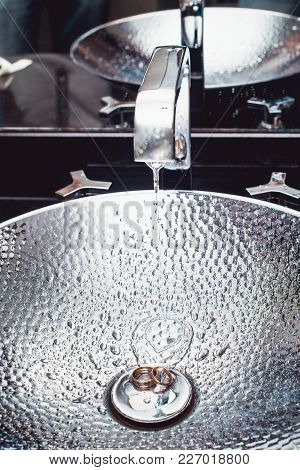 Wedding Rings In A Luxury Chrome-plated Wash Basin. Reflections Of Light. Water Splashes