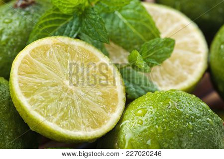 Backgrounds. Close Up Shot Of Wet Limes And Mint. Focus On The Central Part Of Sliced Lime.