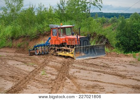 Tractor Bulldozer On A Caterpillar Drive Is Parked In The Mud. Concept Road Construction.