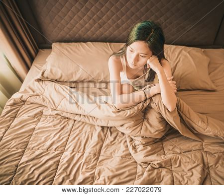 Asian Woman Suffering From Depression On Bed