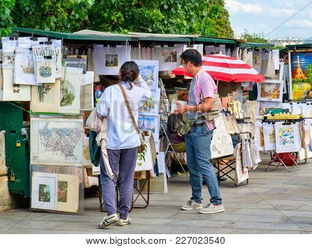 PARIS,FRANCE - AUGUST 1,2017 : Tourists looking at a typical parisian artist paintings on the left bank of the Seine