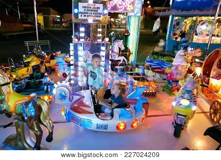 Montanyan, Italy - 16 July 2017: Children's Amusement Rides. Late At Night Children Have Fun.