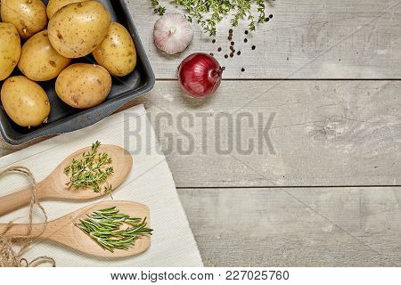 Wooden Spoon With Caraway And Rosemary, Potato, Onion, Garlic On Wooden Background. Top View.