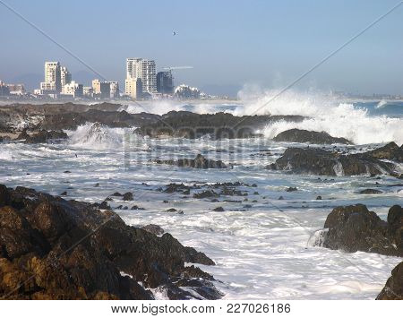 Winter Seascape, With Waves Crashing Over Some Rocks And Spraying Up Into The Air In The Fore Ground