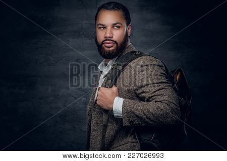 Bearded Black Man In A Suit Holds Backpack.