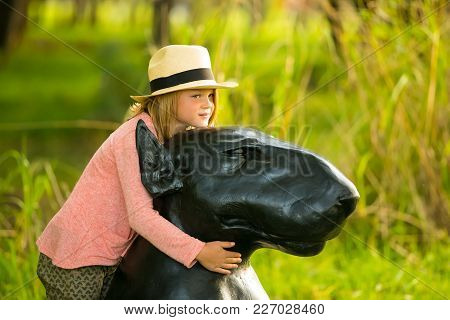 Johannesburg, South Africa, 05/10/2014, Young Girl Hugging A Dog Sculpture At The Winter Sculpture F