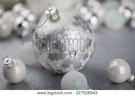 White And Silver Christmas Ornaments With Larger Globe Covered With Star Shapes Formed From Glitter