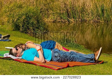 Johannesburg, South Africa, 05/10/2014, Young Couple Lying On A Picnic Blanket At The Winter Sculptu