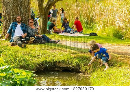 Johannesburg, South Africa, 05/09/2015, A Young Family With Their Kids Playing In A Pond At The Wint