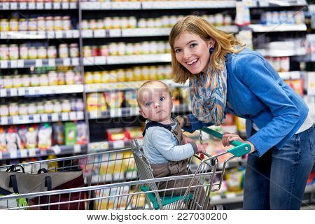 Happy Mother With Baby Staying In Supermarket And Looking Into Camera