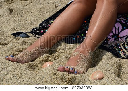Woman Feet In The Sand At The Beach