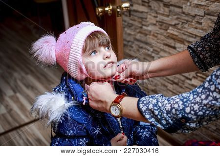 Mother Helps To Dress My Little Girl And Tying Her Hat.