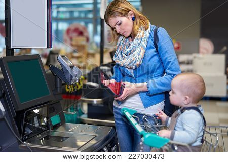 Young Woman With Toddler Staying In Front Of Self Checkout Machine And Looking With Serious Face Int
