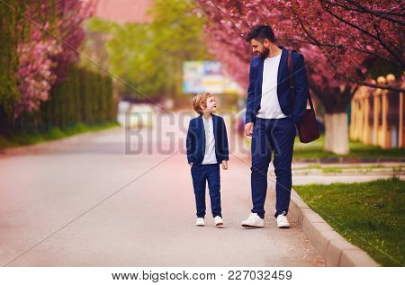 Happy Father And Son Walking Together Along Blooming Spring Street, Wearing Suits