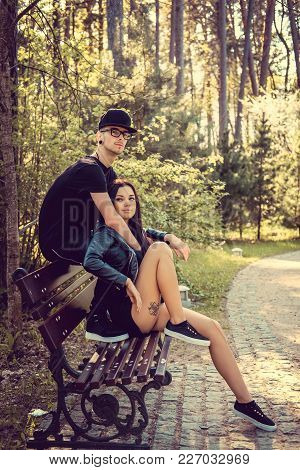 Young Casual Couple Relaxing On A Bech In A Summer Forest.