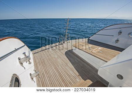 Stern teak decking on a large luxury motor yacht with capstans and ladders