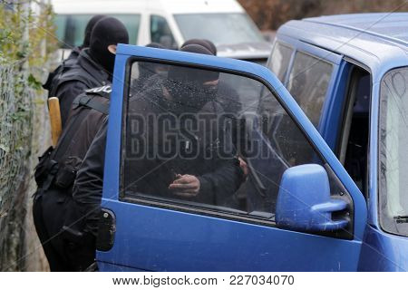 Special law enforcement unit. Special police force units in uniforms, bulletproof vests, firearms and guns. Masked police officers. Special Assault Team during mission. Blue van. poster
