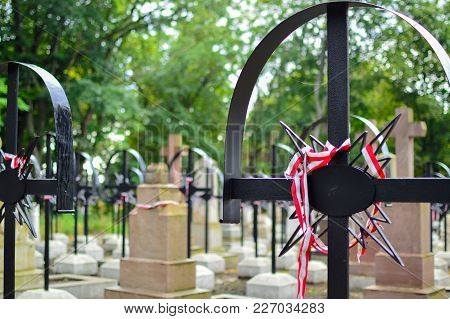 Ribbon With National Colours Of Poland Tied Up To The Cross On The Cemetery. Warsaw Uprising Concept