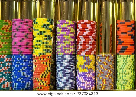 Colourful Roulette Chips In A Casino On A Gambling Table. Lots Of Chips With Different Nomination An
