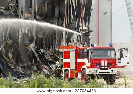 Fire Disaster In A Warehouse. Fire Fighting In An Industrial Area. Red Fire Truck.