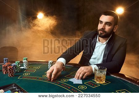 A Young Man In A Business Suit Sitting At The Poker Table. Man Gambles. The Player At The Gaming Tab