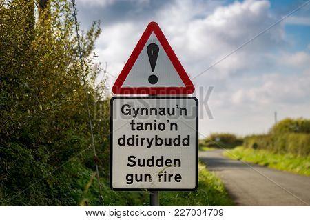 Sign: Sudden Gun Fire (welsh & English), Seen Near Castlemartin In Pembrokeshire, Wales, Uk