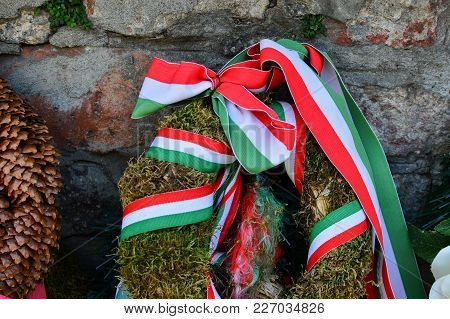 Ribbon With National Colours Of Hungary Tied Up To The Flower Tribute Standing Near To The Castle Wa