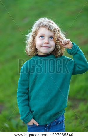 Small blond child with green jersey imagining something in the field