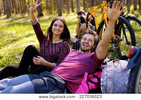 One Male And Two Female Relaxing In A Park After Riding With Bicycles.