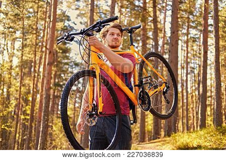 Positive Sporty Male Holds Mountain Bicycle In One Arm Over His Head.