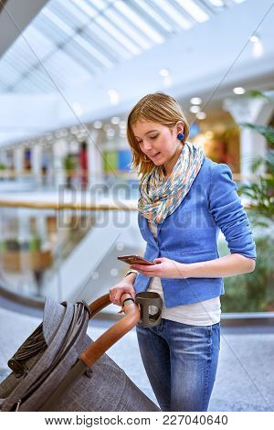 Young Beautiful Woman Staying With Stroller In Shopping Center And Looking On Mobile Phone. Vertical