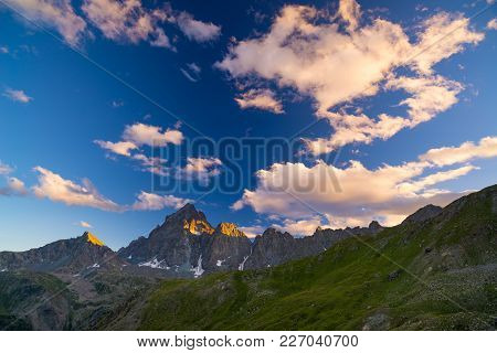 Rocky Mountain Peaks, Ridges And Valleys, The Alps At Sunset. Extreme Terrain Landscape At High Alti