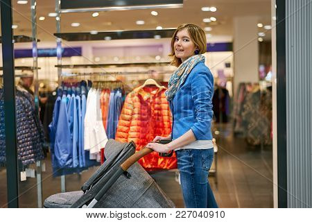Young Beautiful Woman Staying Against Clothing Store With Stroller In Shopping Center And Looking In