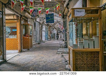 Yazd, Iran - May 5, 2015: A Biker Driving Empty Street Of Bazaar During Afternoon Break.