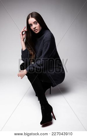 Full Body View Of Young Fashion Model Sitting On The Floor Isolated On White.