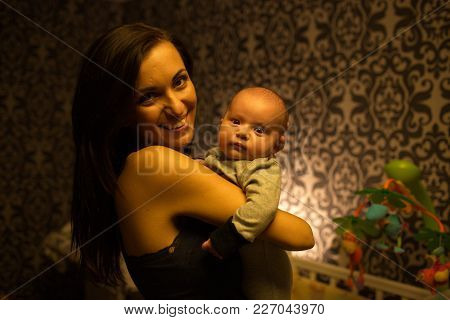 Smiling Young Mother Holding Her Little Boy In Bedroom With Baby Bed And Mobile On Background
