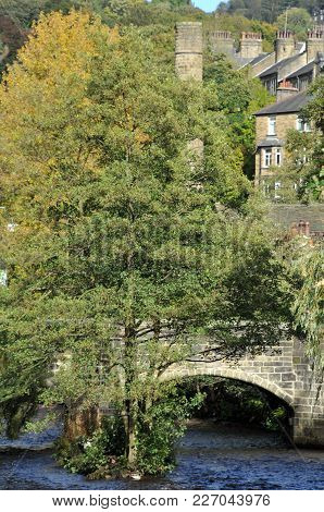 Hebden Bridge Town In Summer With Packhorse Bridge Crossing The River Calder And Stone Buildings In