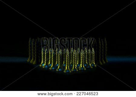 Metal Self-tapping Or Screws On The Table. On A Black Background. Front Rows Of Fasteners Are Lit By