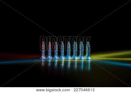 Metal Self-tapping Screws On The Table. The Fasteners Are Illuminated. Light Effect.