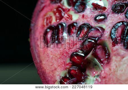 Pomegranate Seeds Close Up Macro Shot Isolated On Black Background.
