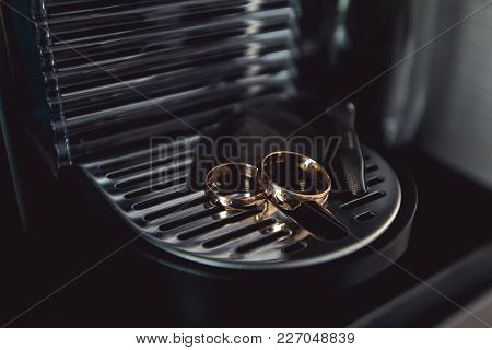 Golden Wedding Rings On A Chrome-plated Coffee Machine.