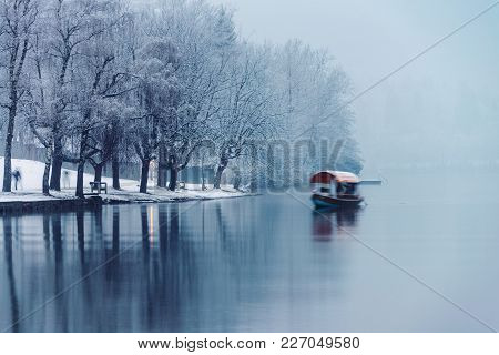 Bled, Slovenia. Foggy Morning In Bled Lake With A Boat, Slovenia. Fog Over The Forest. Famous Place