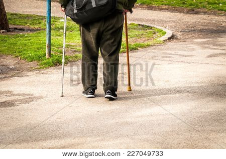 Old Man Walk Alone And Depressed Down The Street With Two Walking Stick Or Cane View From Back