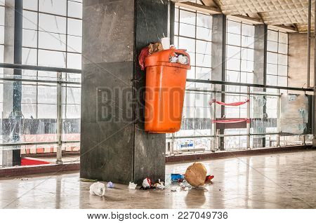 Orange Plastic Garbage Can With Overflow Junk And Litter On The Ground Polluting Indoor Space Of The