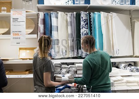 Moscow, Russia - February 10, 2018: Woman And Man Choose Liked Tablecloth For Dining Table In Ikea C
