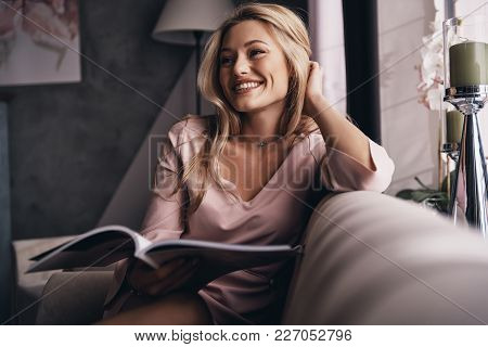 Glowing With Happiness. Attractive Young Woman In Elegant Dress Keeping Hand In Hair And Smiling Whi