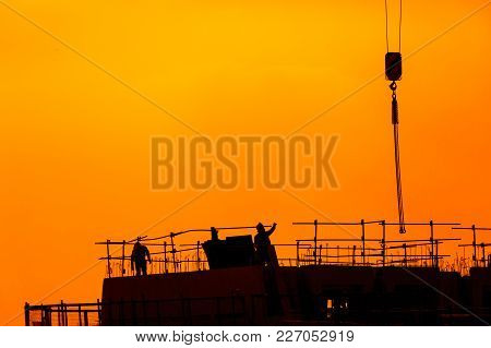 Building Workers Working On A Building Under A Beautiful Sunset. Chinese Shadow Effect.