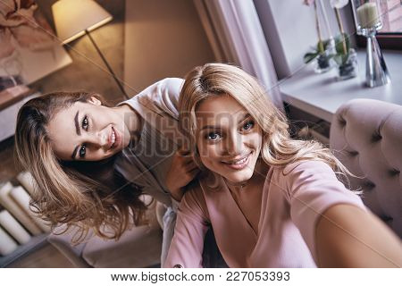 Capturing Happy Moments.  Top View Self Portrait Of Attractive Young Women Smiling And Looking At Ca