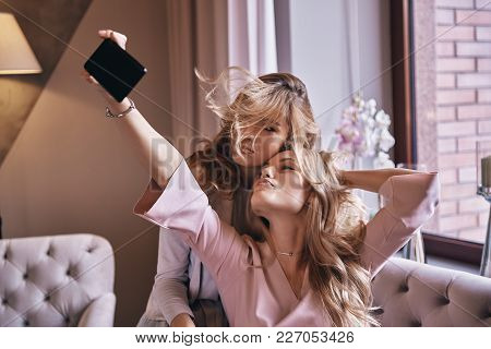 Selfie Time! Playful Young Women In Elegant Dresses Taking Selfie And Smiling While Sitting On The S