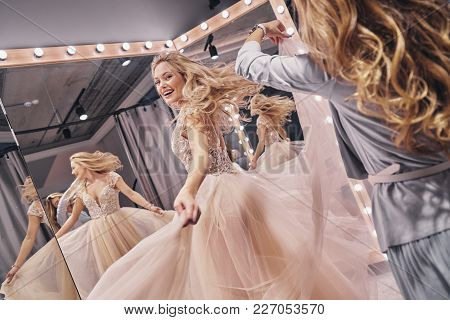 Fits Just Perfect.  Attractive Young Woman Smiling While Her Girlfriend Adjusting Her Wedding Dress